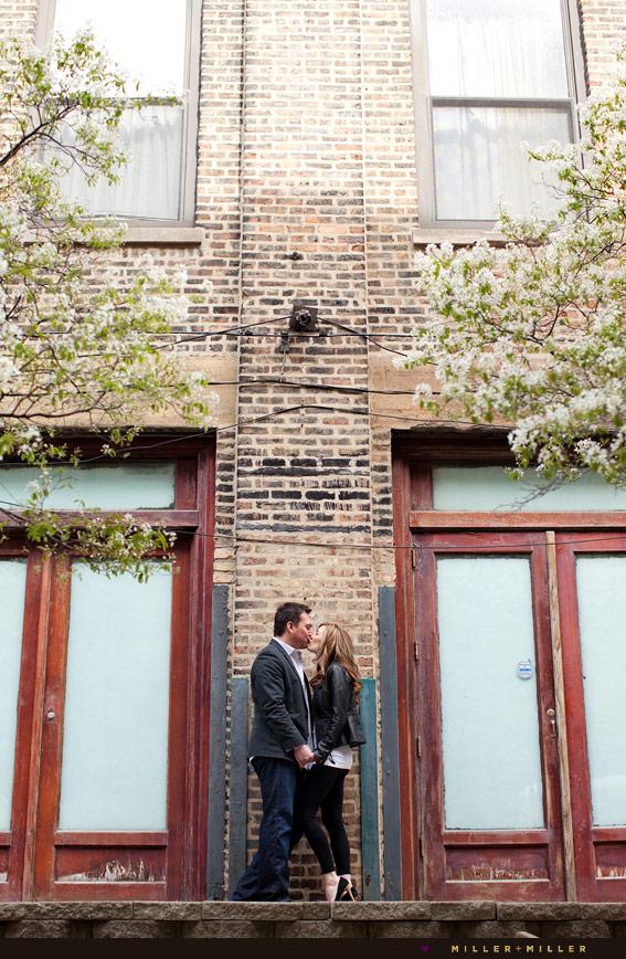 couple kissing brick wall
