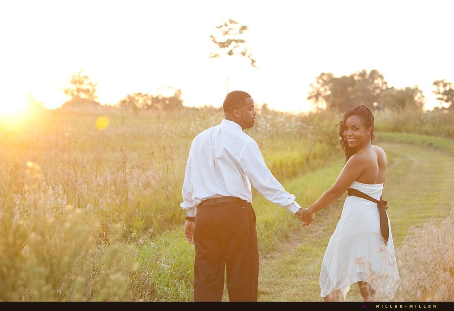 couple walking meadow sunset