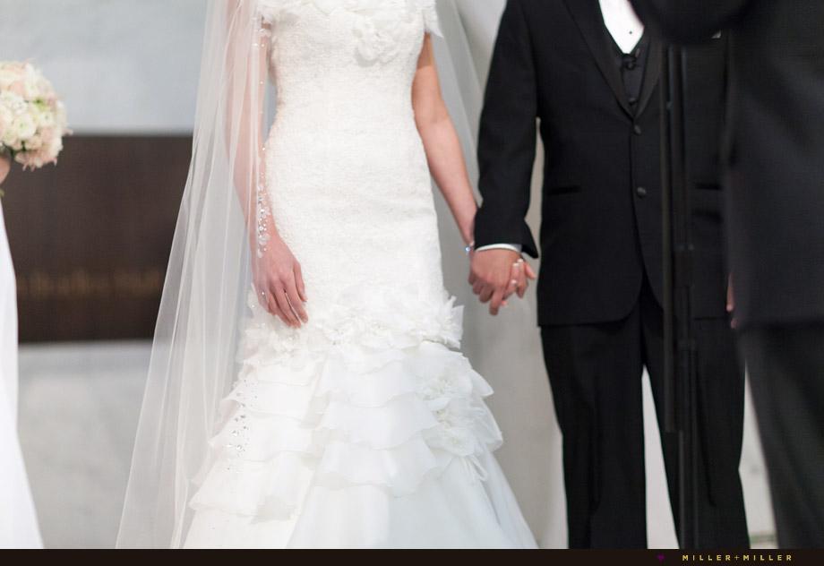 bride groom holding hands at alter