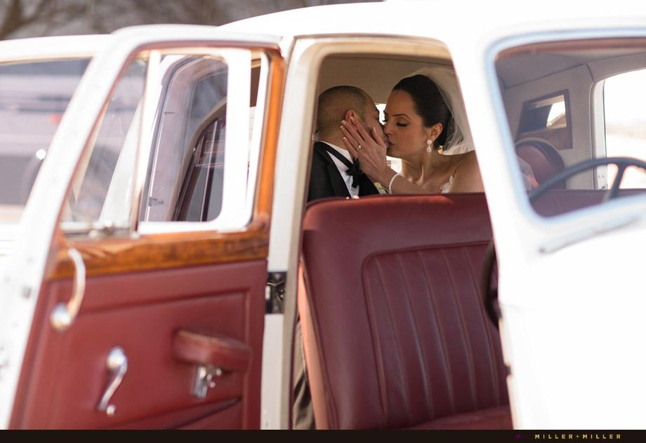 bride groom kissing inside classic car