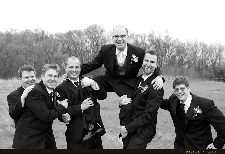 groomsmen carrying groom shoulders