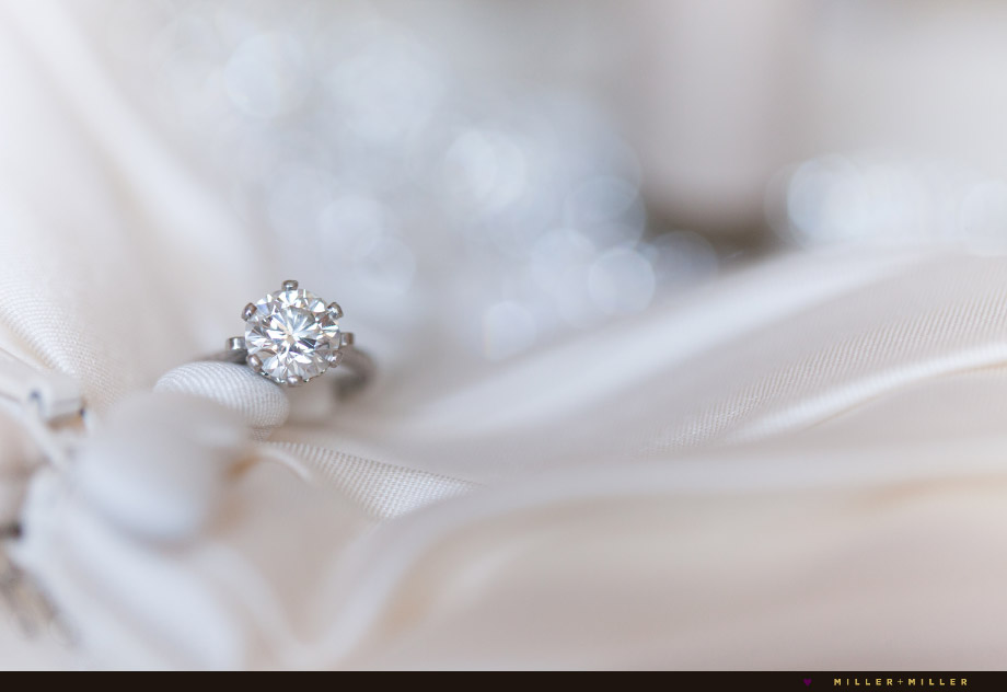 round diamond ring photographed on gown buttons