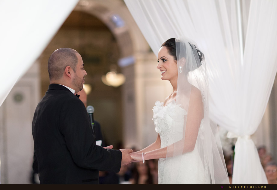 vows under draped white fabric