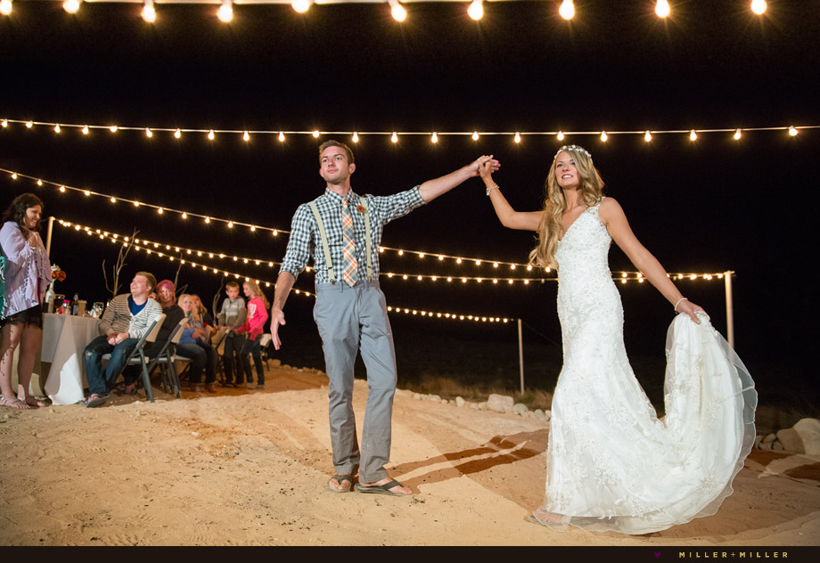 bride groom dancing under string lights beach