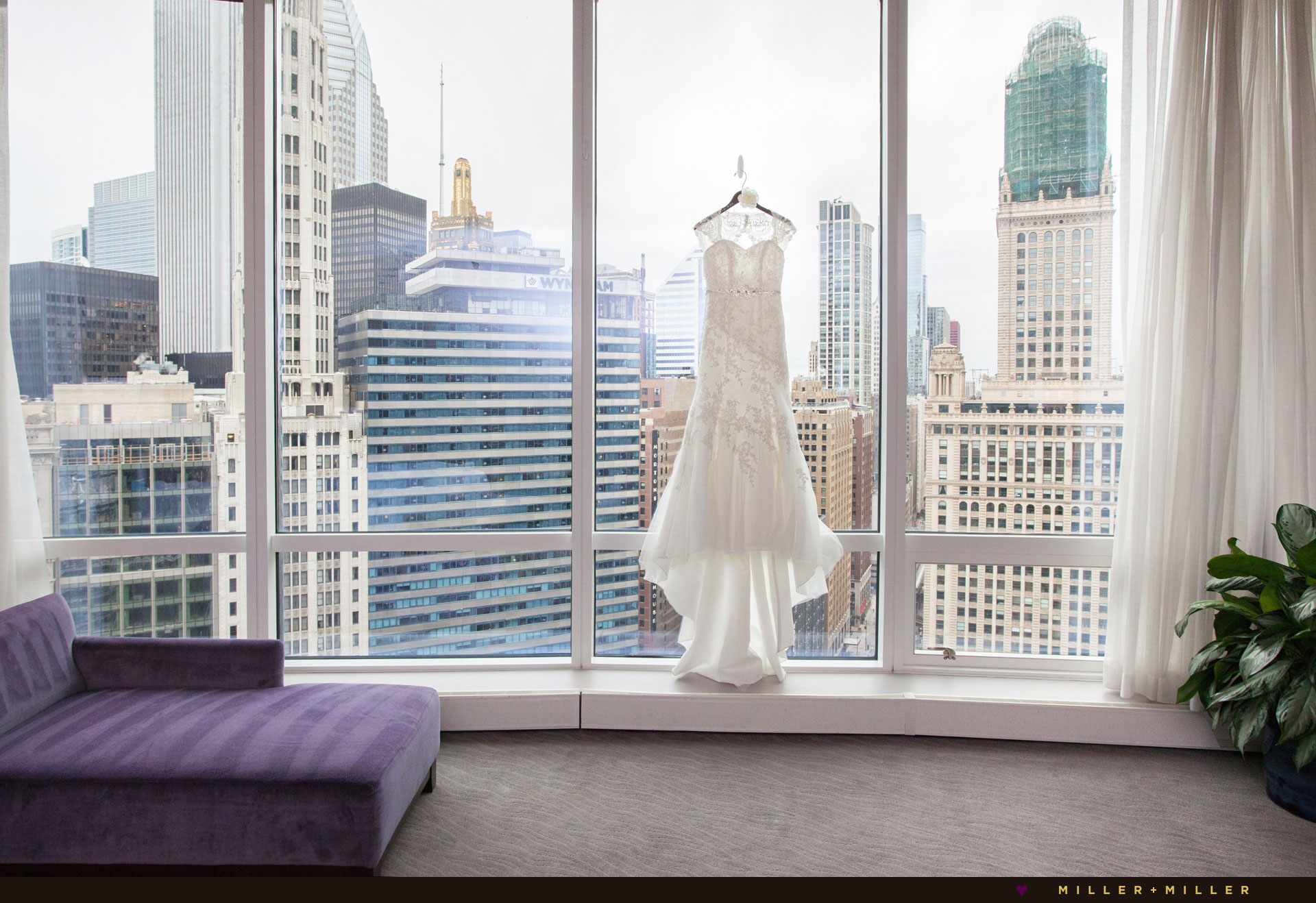 brides dress hangs window skyline